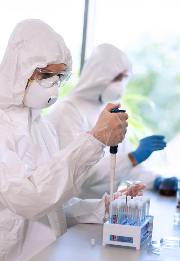 Scienziati nei vestiti di protezione e maschere che lavorano nel laboratorio di ricerca facendo uso dell'attrezzatura di laborato fotografia stock libera da diritti