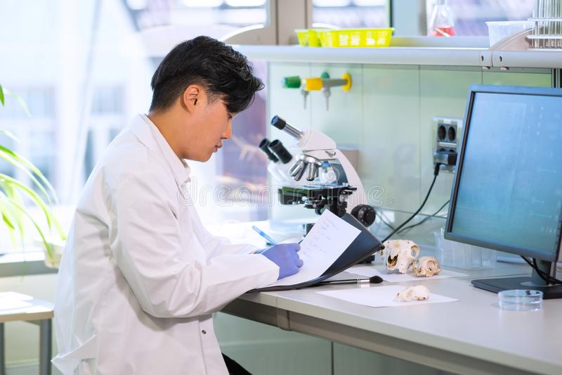 Scienziato asiatico che lavora nel laboratorio Medico che fa ricerca in microbiologia Strumenti del laboratorio: microscopio, pro fotografie stock libere da diritti