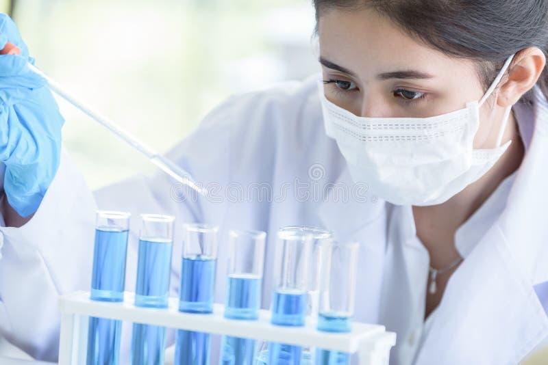 Scienziato asiatico dello studente della ragazza che ricerca e che impara in un laboratorio fotografie stock