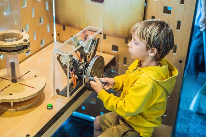 Scienziato astuto del ragazzo che fa gli esperimenti fisici in laboratorio Concetto educativo scoperta fotografia stock