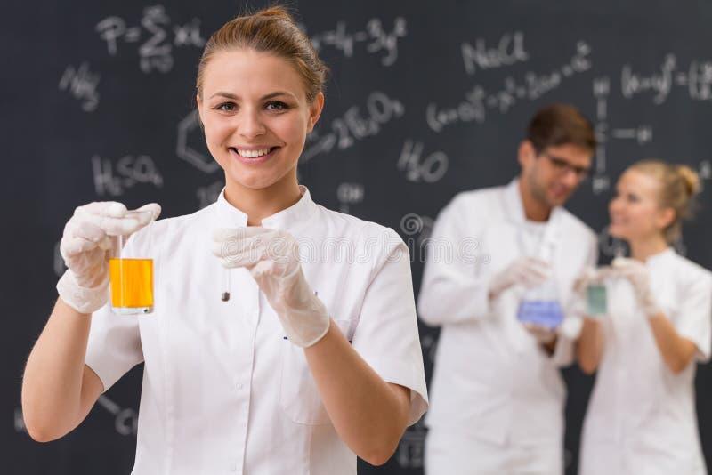 Scienziato che tiene una vetreria per laboratorio con liquido arancio fotografia stock