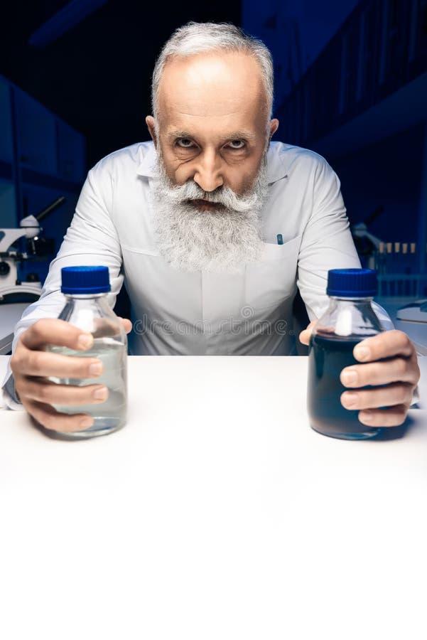 Scienziato diabolico con le bottiglie con i reagenti che esaminano macchina fotografica nel luogo di lavoro fotografia stock libera da diritti