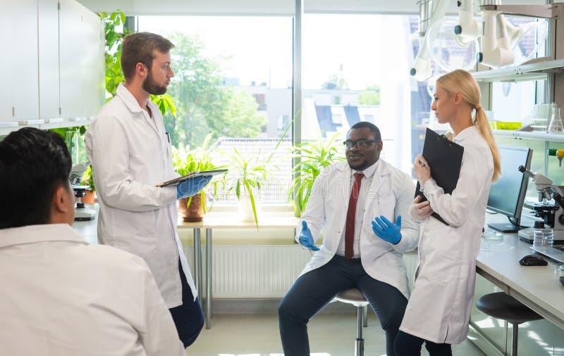 Scienziato e studenti che lavorano nel laboratorio Aggiusti gli interni d'istruzione per fare il sangue che analizza la ricerca b immagini stock libere da diritti