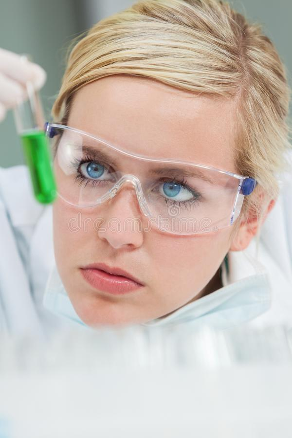 Scienziato femminile & provetta verde in laboratorio immagini stock