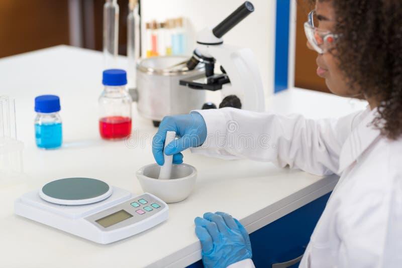 Scienziato femminile Using Mortar Working in laboratorio che fa la polvere per l'esperimento, ricercatore Mix Race dei prodotti c immagini stock