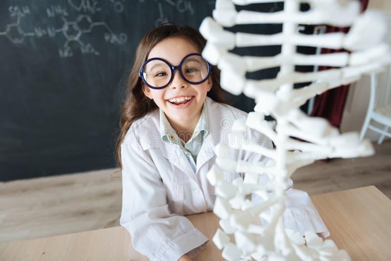 Scienziato giovane carismatico che esplora il modello del DNA in laboratorio fotografie stock