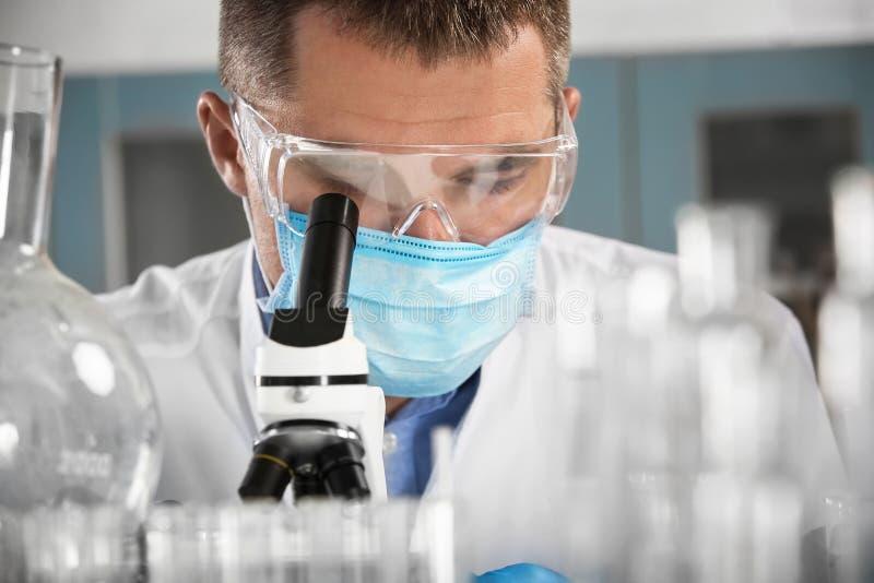 Scienziato maschio con funzionamento del microscopio nel laboratorio immagine stock