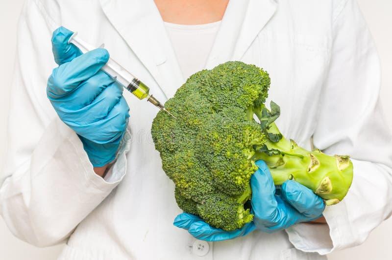 Scienziato OMG che inietta liquido dalla siringa nei broccoli immagine stock libera da diritti