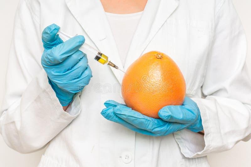 Scienziato OMG che inietta liquido dalla siringa nel pompelmo immagini stock