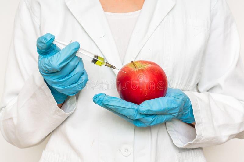 Scienziato OMG che inietta liquido dalla siringa nella mela immagini stock libere da diritti