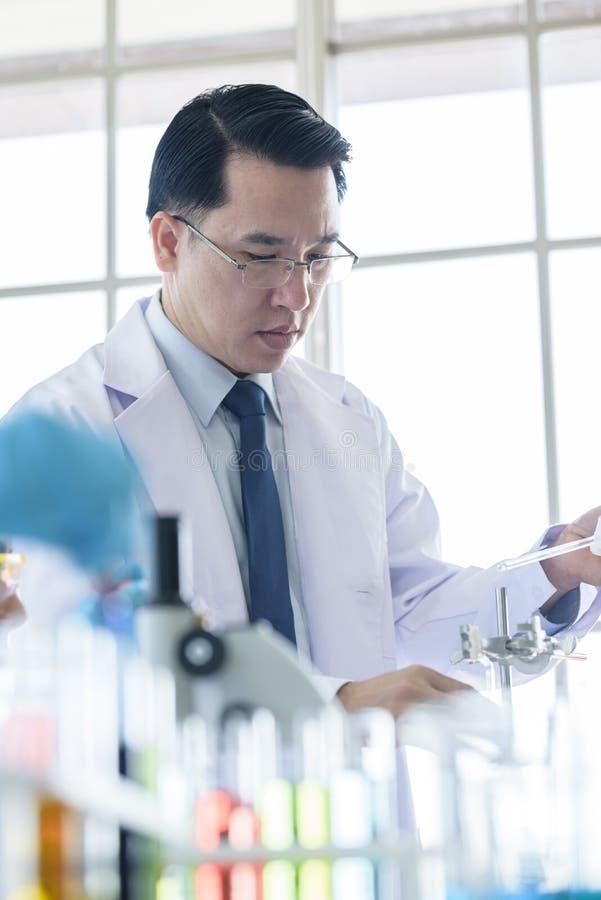 Scienziato senior asiatico che ricerca e che impara in un laboratorio immagini stock libere da diritti