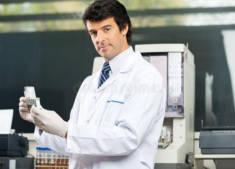 Scienziato sicuro Analyzing Urine Samples in laboratorio fotografia stock