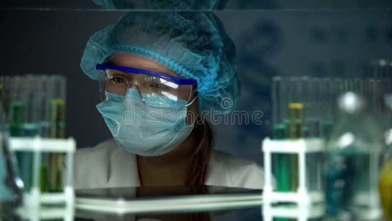 Scienziato in uniforme protettiva che esamina i campioni in tubi, industria chimica fotografia stock
