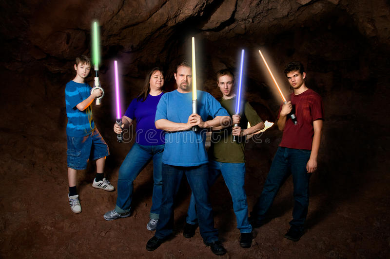SciFi Family With Light Swords. A science fiction loving family poses for a family portrait with pretend light swords in this composite image royalty free stock photo