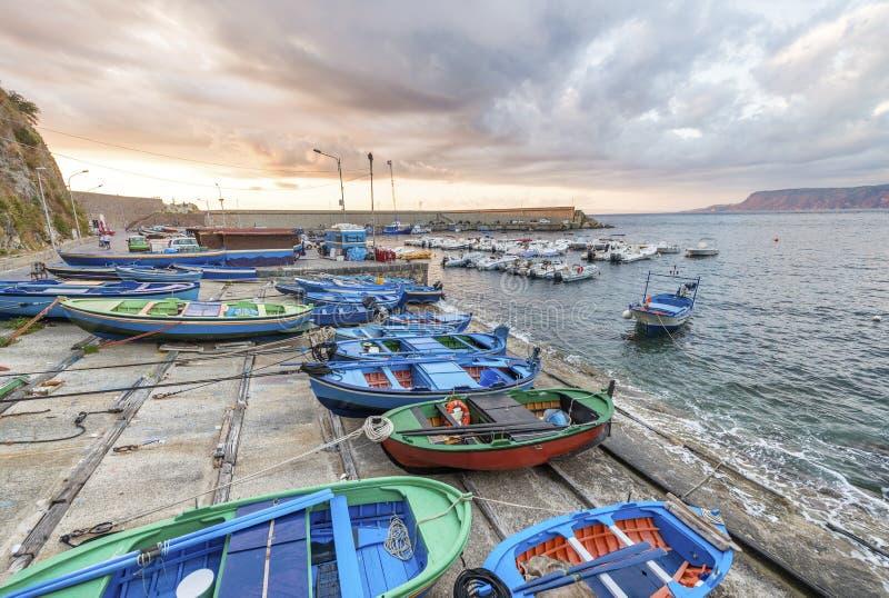 Scilla kustlinje och fartyg i Chianalea på solnedgången, Calabria, Ita royaltyfri foto