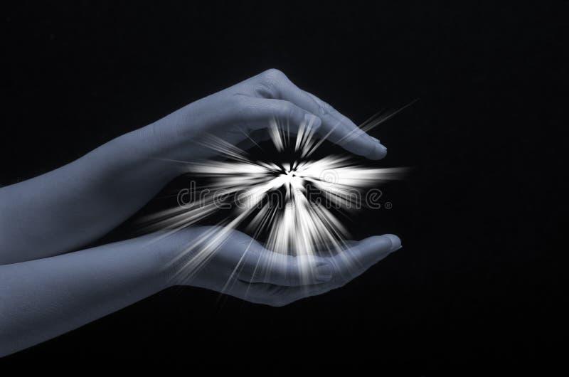 Scintilla di speranza in una mano della donna su fondo scuro La luce di fede Luce di protezione fotografia stock libera da diritti