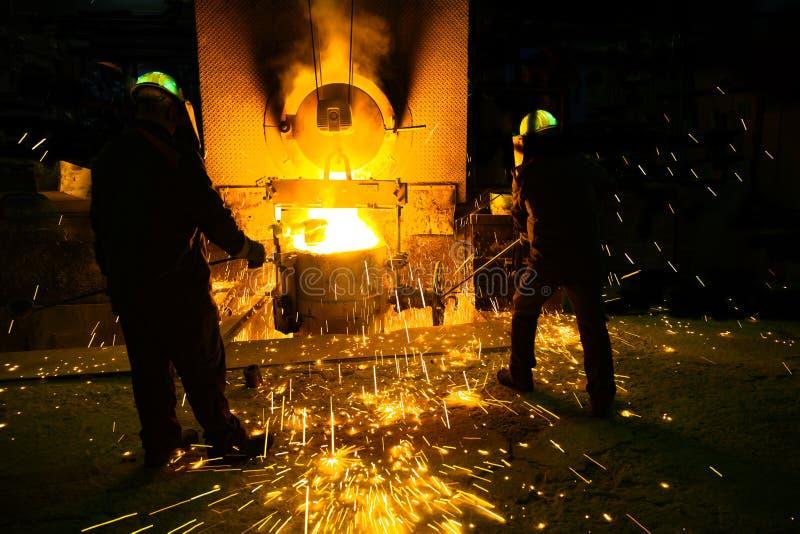 Scintille da acciaio di fusione, uomini che guardano acciaio di fusione scintillante in fornace della fonderia fotografia stock