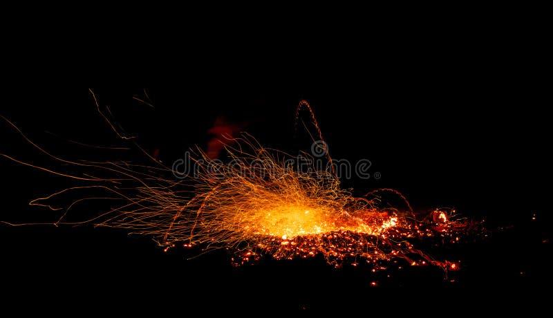 Scintille dall'esplosione dei tizzoni del fuoco su un fondo nero fotografia stock