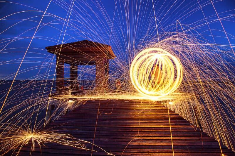 Scintille dorate calde che volano dall'uomo che fila lana d'acciaio bruciante immagine stock libera da diritti