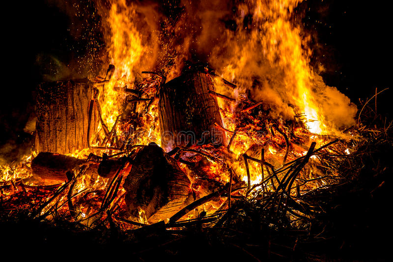 Scintille e lingue di fuoco sui rami e sui tronchi che bruciano in una b immagine stock libera da diritti