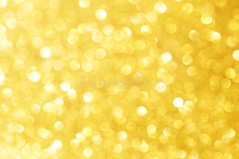 Scintilli dorati della scintilla con effetto del bokeh e selectieve fuoco Fondo festivo con le luci luminose dell'oro, bolla del  fotografie stock libere da diritti
