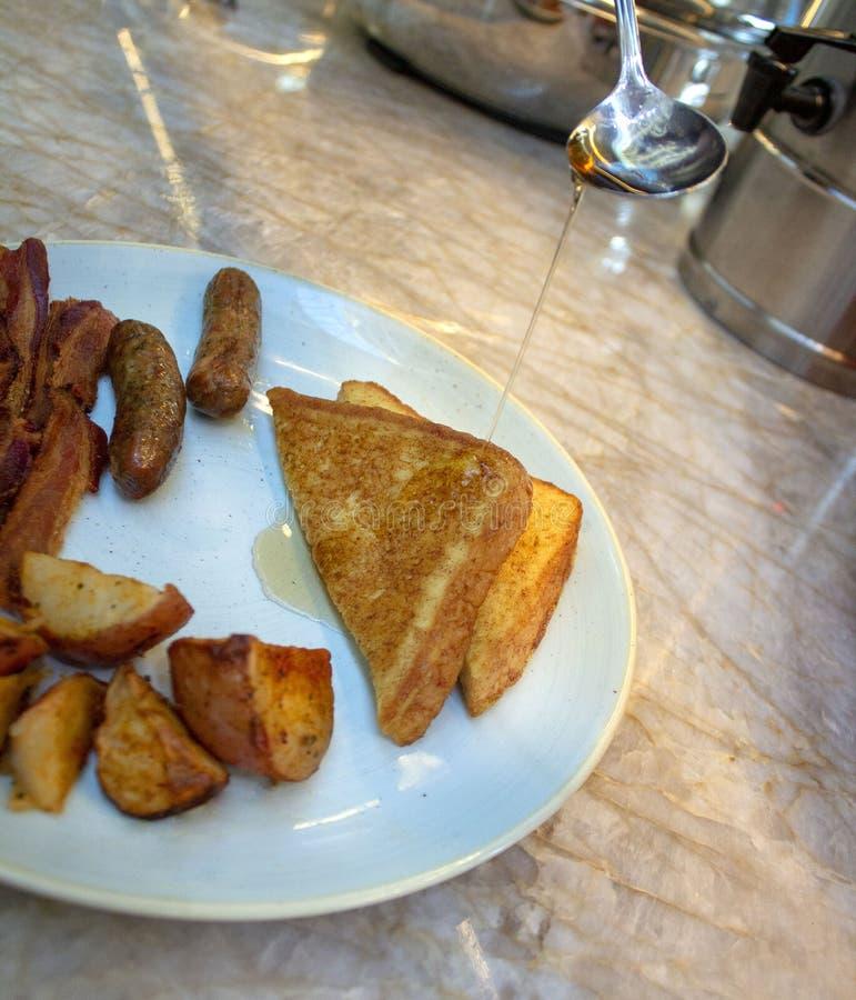 Sciroppi il versamento sul pane inzuppato in latte/uova e zucchero e fritto in padella fotografia stock