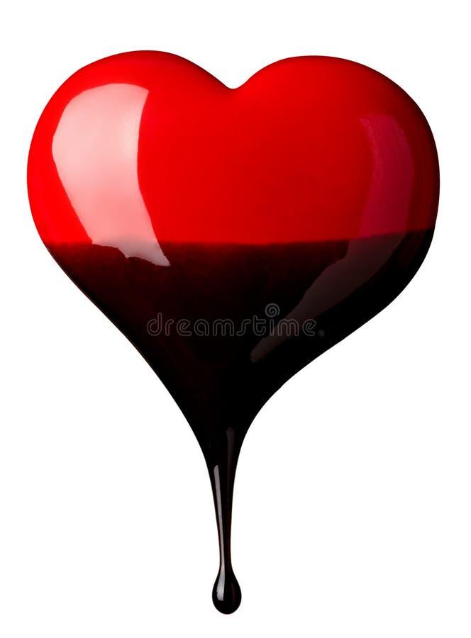 Sciroppo di cioccolato che cola sulla figura del cuore fotografia stock libera da diritti