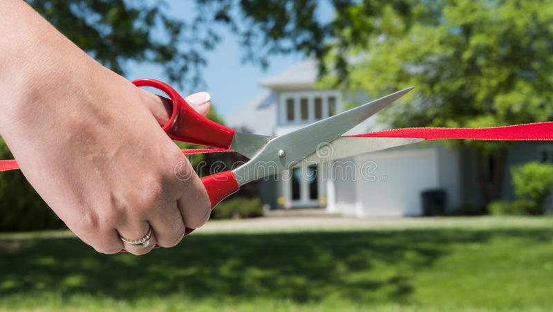 A scissor-cut arm cuts a red ribbon, and a typical American house is visible in the background. Housewarming and buying. A home concept stock photography