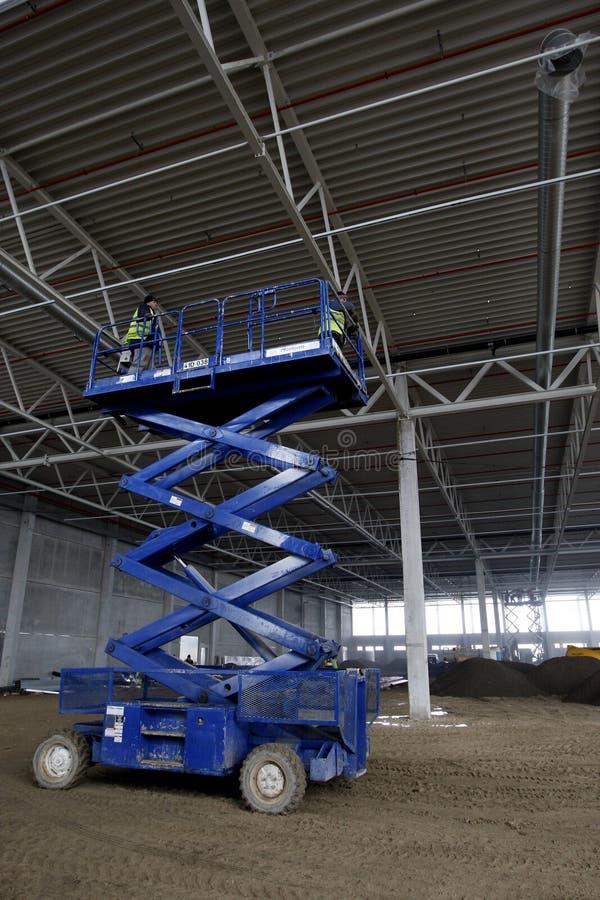 Scissor la piattaforma dell'elevatore all'interno di fabbricato industriale fotografie stock libere da diritti