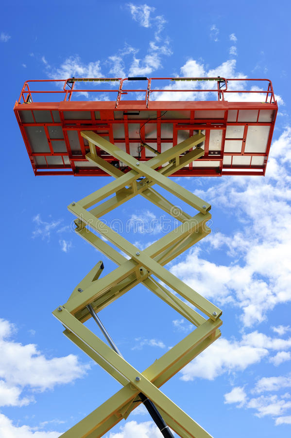 Scissor lift platform. With hydraulic system at maximum height range painted in orange and beige colors, large construction machine, heavy industry, white stock image