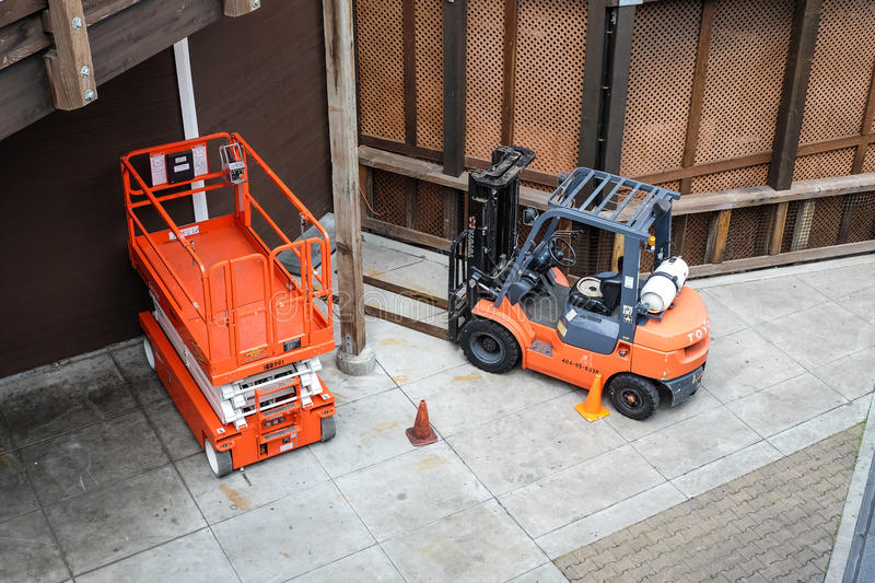 A scissor lift. SAN FRANCISCO - MAY, 2017: A scissor lift and a forklift parked in a warehouse royalty free stock image