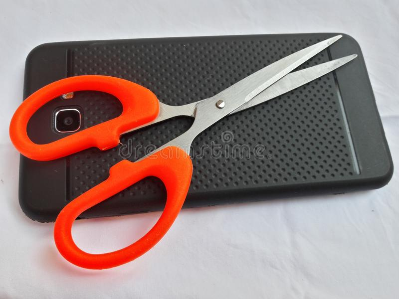 Scissor med mobiltelefonen fotografering för bildbyråer