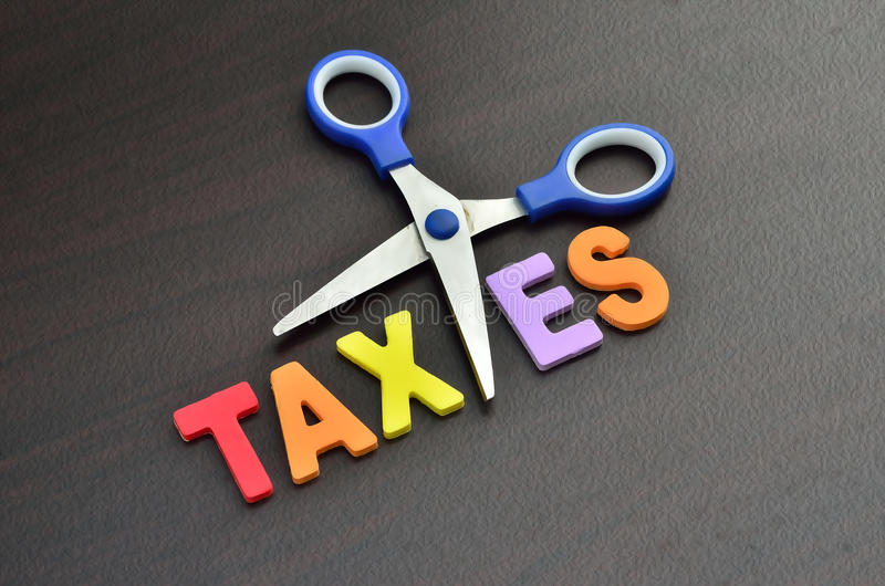 Scissors and the alphabet TAXES. Image of scissors and the alphabet TAXES royalty free stock photo