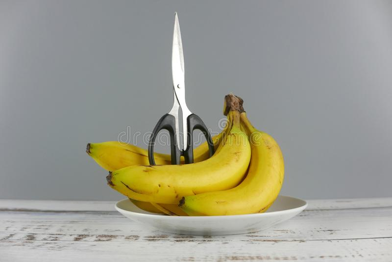 Scissors and bunch of bananas on wooden background. Healthcare concept stock images