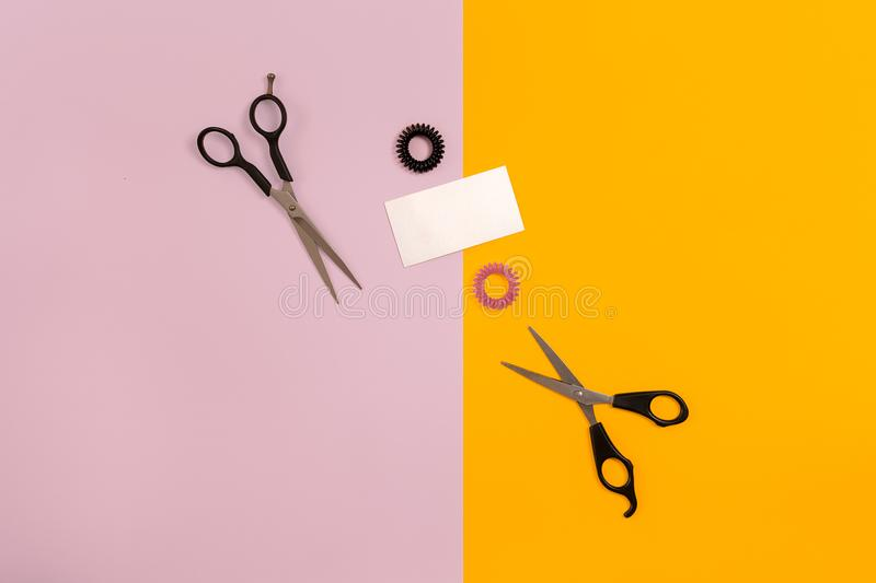 Scissors on the color pink, yellow paper background. Top view. Copy space. Still life. Mock-up. Flat lay stock image