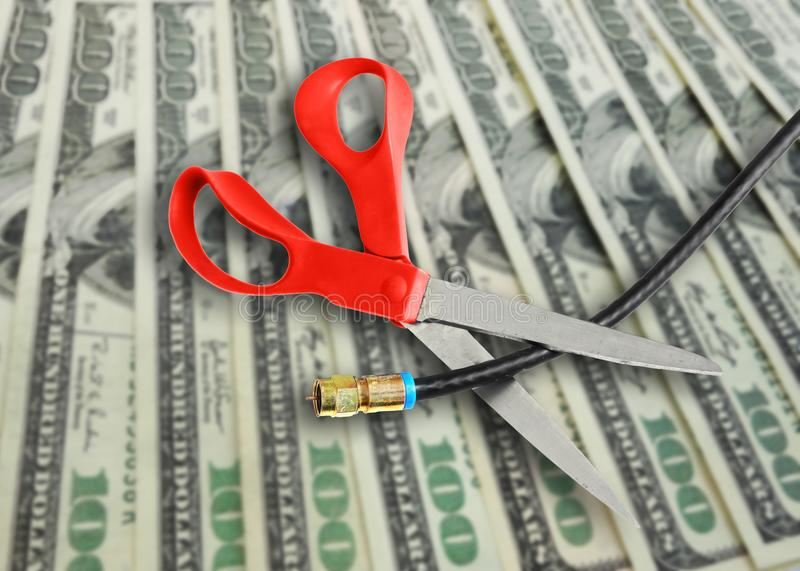 Cutting the cable. Scissors cutting a coax cable on cash background -- cutting the cord to save money concept stock images
