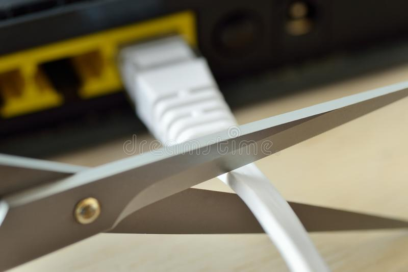 Scissors cutting internet modem router cable - Concept of network and data protection. Scissors cutting internet modem router cable. Concept of network and data stock photography