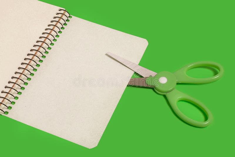 Scissors cutting sheet of paper. Pair of colored plastic scissors with green handle cutting a sheet of paper of a notebook lying on a green background. free royalty free stock photo