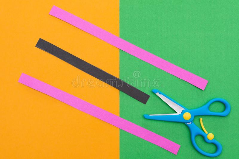 Scissors & hand cut paper straps on colorful scrapbook. Scissors and hand cut paper straps on colorful scrapbook royalty free stock images