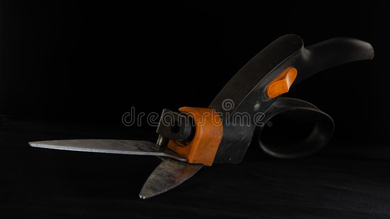 Scissors for a lawn on a black background stock images