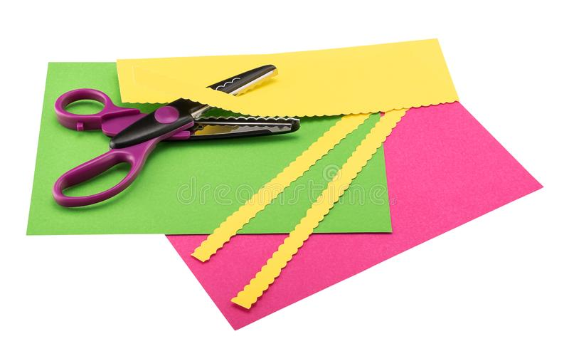 Scissors, paper edgers, lying on color construction paper royalty free stock image