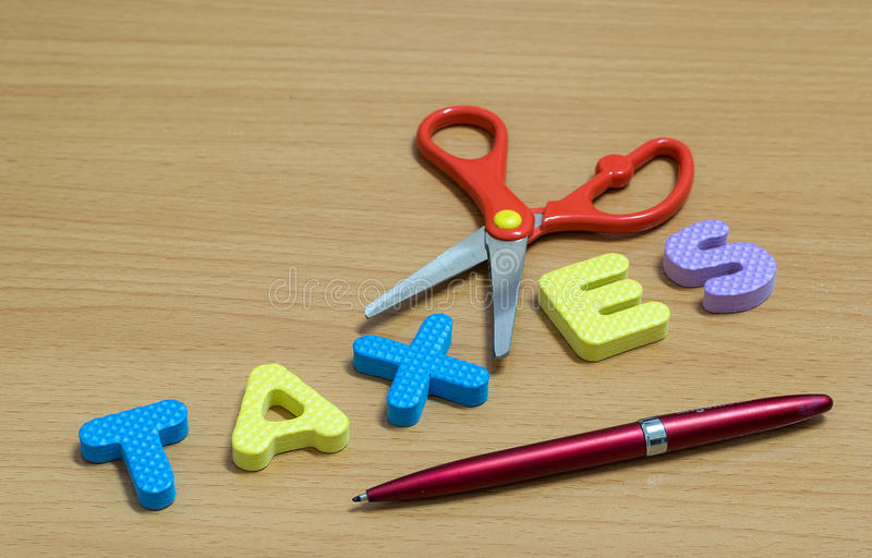 Scissors and the plastic alphabet TAXES. royalty free stock photography