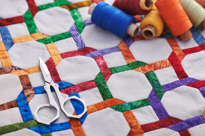 Scissors and spools of thread lying on fragment quilt top sewn by hand from geometric figures royalty free stock images