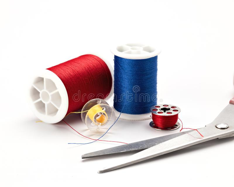 Scissors and thread on a white surface used in sewing stock photos