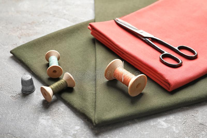 Scissors, threads and fabric on grey table. Tailoring equipment royalty free stock photos