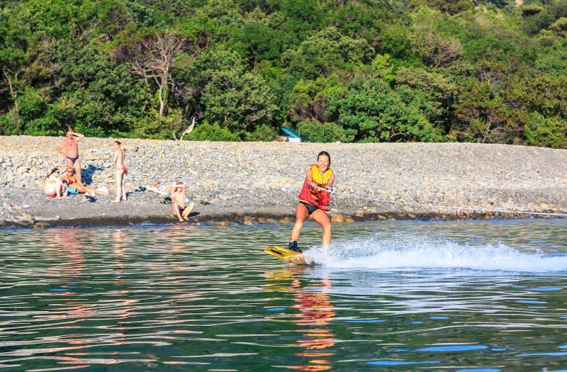 Scivolate del wakeboarder della giovane donna sulla superficie piana del mare rimorchiata in imbarcazione a motore di wakeboard a immagine stock libera da diritti