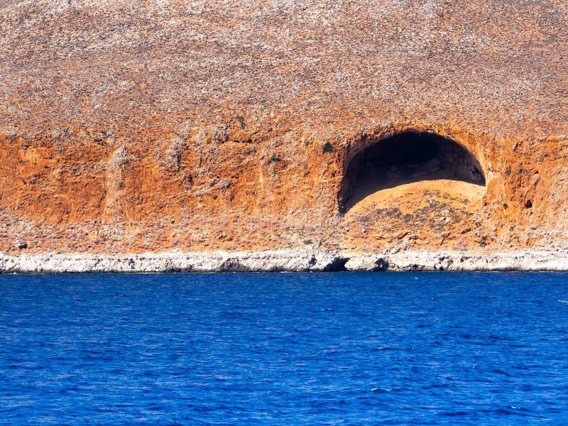 Scogliere arancio della roccia ed acque blu profonde immagine stock