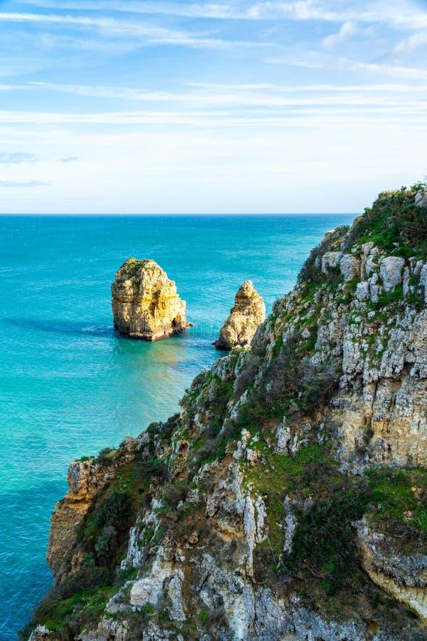 Scogliere con vegetazione e rocce nell'oceano alla costa di Lagos, Portogallo fotografia stock
