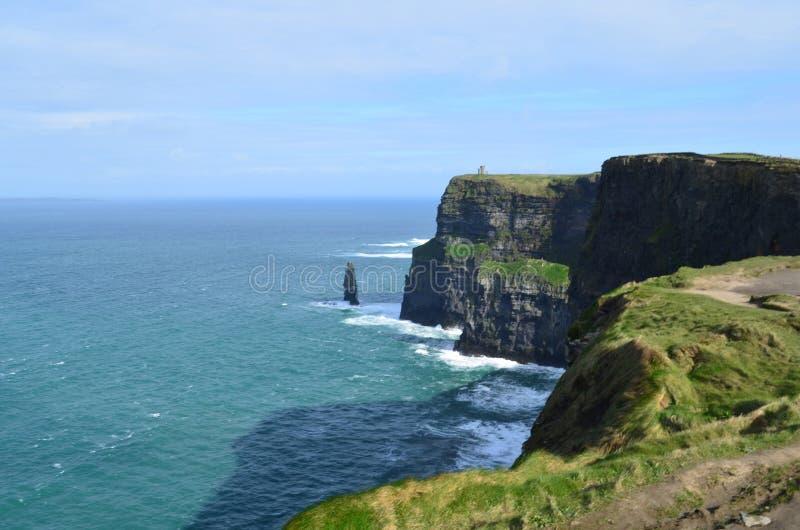 Scogliere graziose del mare in Irlanda con i cieli blu ed acque immagini stock libere da diritti