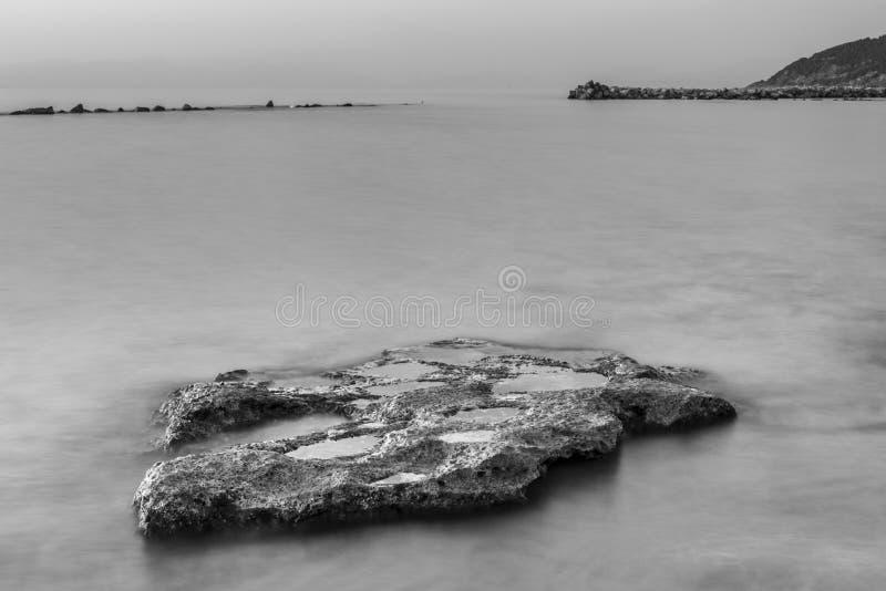 Scogliere sotto il cielo blu, primo piano del mare della foto fotografia stock